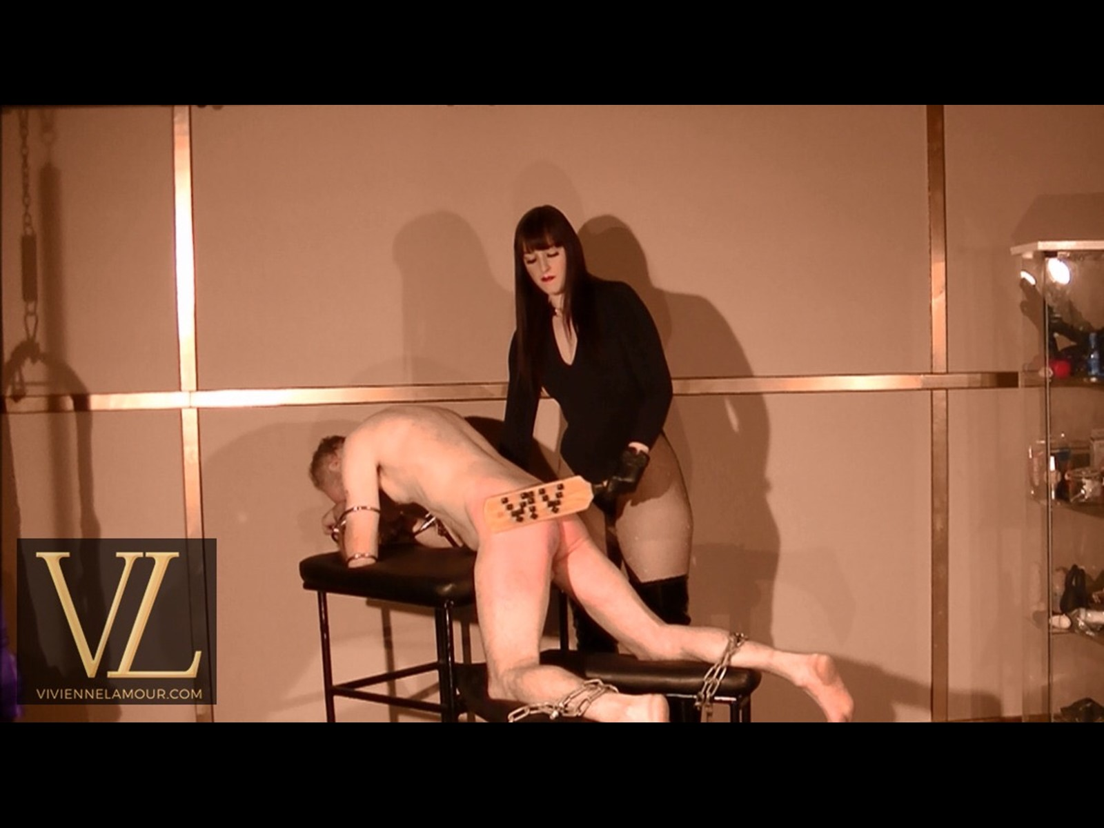 Using the Goddess Vivienne paddle with stones to make the slave on spanking bench suffer in fetish studio for hire