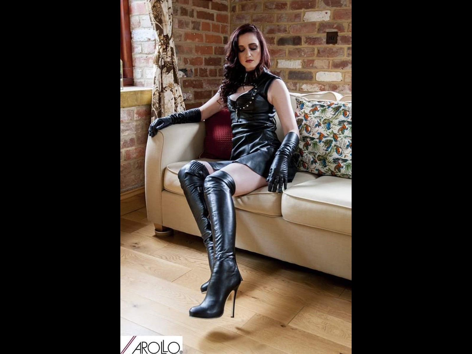 Mistress Vivienne of Derby posing in The Summerhouse in Arollo Leather Boots - Leather Dress, Gloves, Jacket