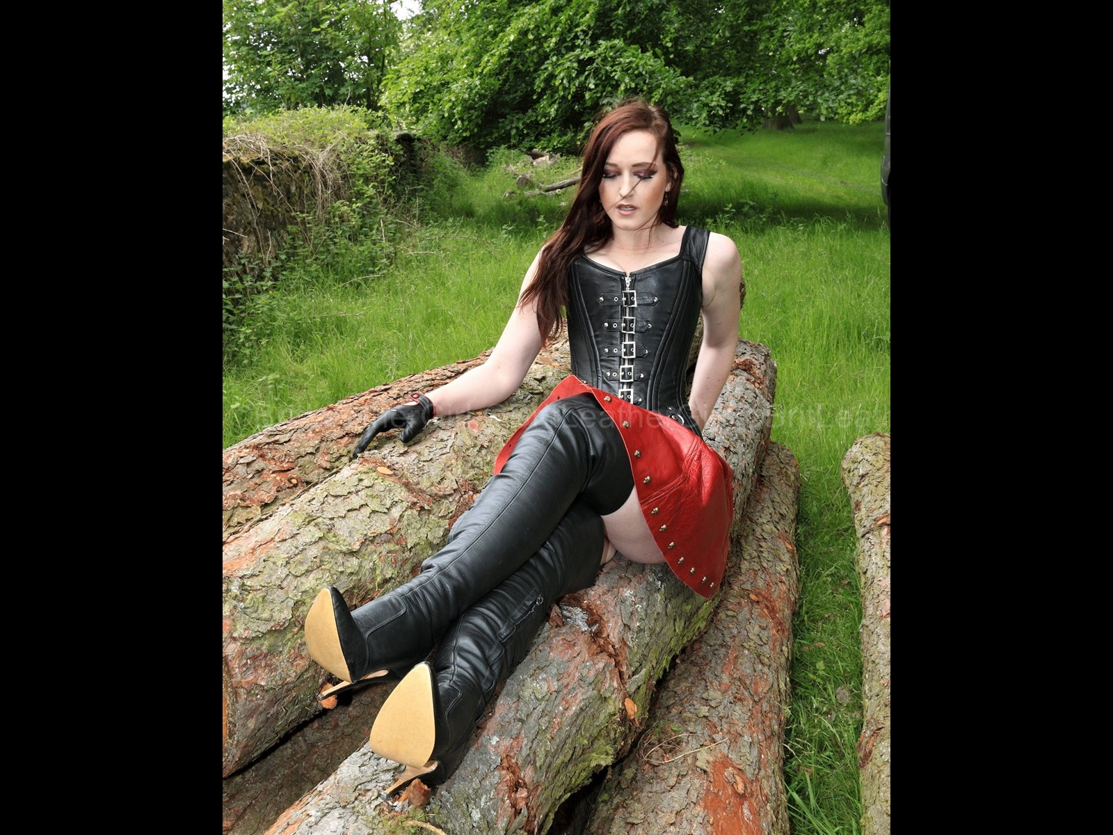 Outdoors on a log in Genuine Leather Boots and a Leather Corset with Buckles and Skirt
